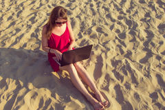 Young woman with laptop computer on the beach. Downshifting and Royalty Free Stock Photo