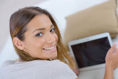 Young woman with laptop on couch Royalty Free Stock Images