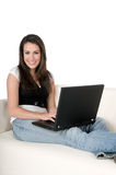Young woman with laptop on couch, isolated Stock Image