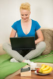 Young woman  with laptop on the couch in living room Stock Images