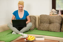 Young woman  with laptop on the couch in living room Stock Photo