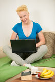 Young woman  with laptop on the couch in living room Stock Image