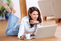 Young woman with laptop and a cup of coffee on the floor Stock Photos