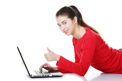 Young woman with laptop gesturing ok Stock Photos