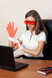 Young woman with the laptop in gloves and orange. Young woman sits at a table at office in orange glasses dresses gloves and looks in the laptop. Business style Stock Images