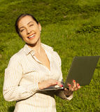 Young woman with laptop on green grass Royalty Free Stock Photos