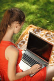 Young woman with laptop on green grass at park. Engaged in teaching Stock Photo