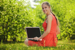 Young woman with laptop on green grass at park. Engaged in teaching Royalty Free Stock Image