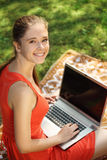 Young woman with laptop on green grass at park. Engaged in teaching Stock Images