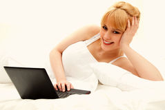 Young woman with laptop in her bed Stock Photography