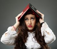 Young woman with a laptop on her head Stock Photography