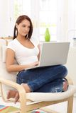 Young woman with laptop at home Stock Images