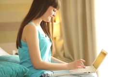 Young woman with laptop looking at camera and stock video