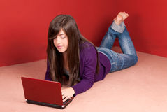 Young woman with laptop lying on floor at home Stock Photo