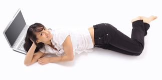 Young woman with laptop lying on the floor . on white. Photo with copy space Royalty Free Stock Photo