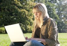 Young woman with laptop on a meadow Stock Photos