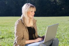 Young woman with laptop on a meadow Stock Image