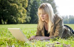 Young woman with laptop on a meadow Stock Images