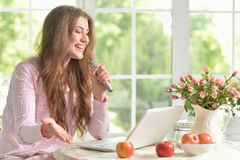 Young woman with laptop and microphone Stock Image
