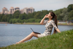Young woman with laptop and mobile phone in park. Stock Photos
