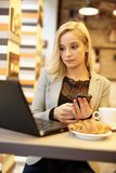 Young woman with laptop and mobile. Young woman using laptop computer and mobilephone while having croissant Stock Images