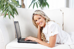 Young woman with laptop in the new apartment Stock Image