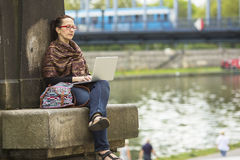 Young woman with laptop outdoors. Preparation for exams. Royalty Free Stock Photos