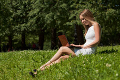 Young woman  with the laptop in park . Stock Image