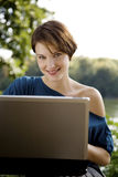 Young woman with laptop in park royalty free stock photo