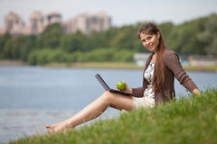 Young woman with laptop in the park. Stock Image
