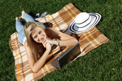 Young woman with laptop. In park stock photo