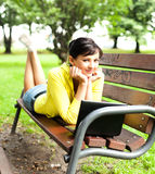 Young woman with laptop in the park Royalty Free Stock Photography