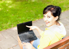 Young woman with laptop in the park Royalty Free Stock Image