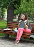 Young Woman with a Laptop in the Park. Young student woman hugging her laptop while sitting on a bench in a park Stock Image