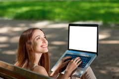 Young woman with laptop in the park Stock Photos
