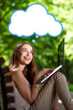 Young woman with laptop in the park Stock Image