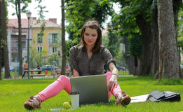 Young Woman with a Laptop in the Park. Young woman working on a laptop outside in an urban park Stock Photos