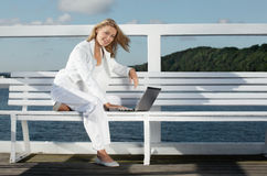 Young woman with laptop. On the pier royalty free stock photography