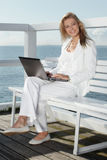 Young woman with laptop. On the pier stock photography