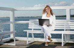 Young woman with laptop. On the pier stock photos