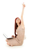 Young woman with laptop pointing up, full length Stock Image