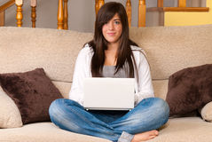 Young woman with laptop portable sitting on sofa Stock Photos