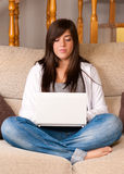 Young woman with laptop portable sitting on sofa Royalty Free Stock Image
