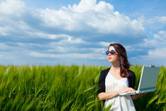 Young woman with laptop. Portrait of young beautiful woman with laptop in the field Stock Images