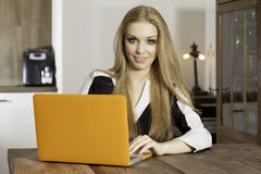 Young woman with laptop. Portrait of a smiling young woman with laptop in the kitchen Stock Photos