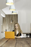 Young woman with laptop. Portrait of a smiling young woman with laptop in the kitchen Stock Image
