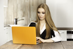 Young woman with laptop. Portrait of a smiling young woman with laptop in the kitchen Royalty Free Stock Photo