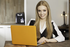 Young woman with laptop. Portrait of a smiling young woman with laptop in the kitchen Royalty Free Stock Images