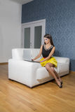 Young woman with laptop in the room. Young woman with laptop on the sofa Royalty Free Stock Photo