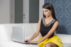 Young woman with laptop in the room. Young woman with laptop on the sofa Royalty Free Stock Images